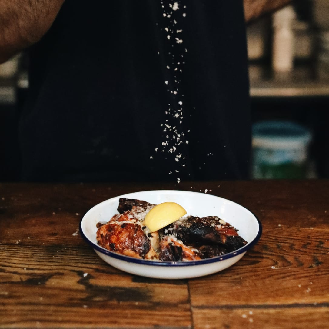 Salt being sprinkled onto a plate of cooked chicken.