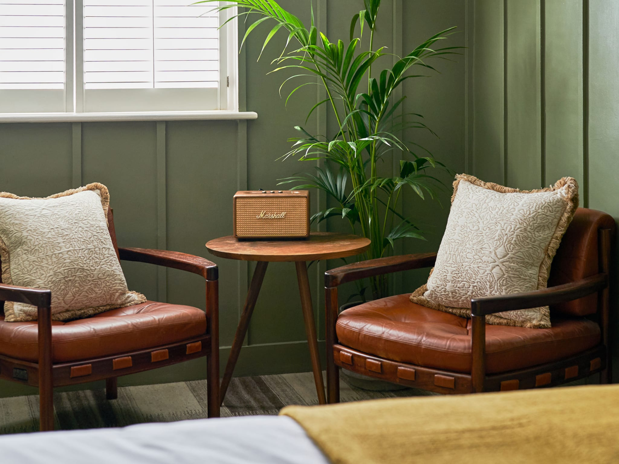 A coffee table and two chairs at the end of a bed in a green bedroom.