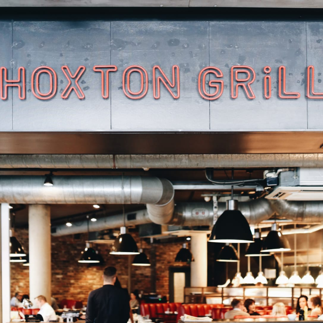 A neon sign saying Hoxton Grill above a restaurant.