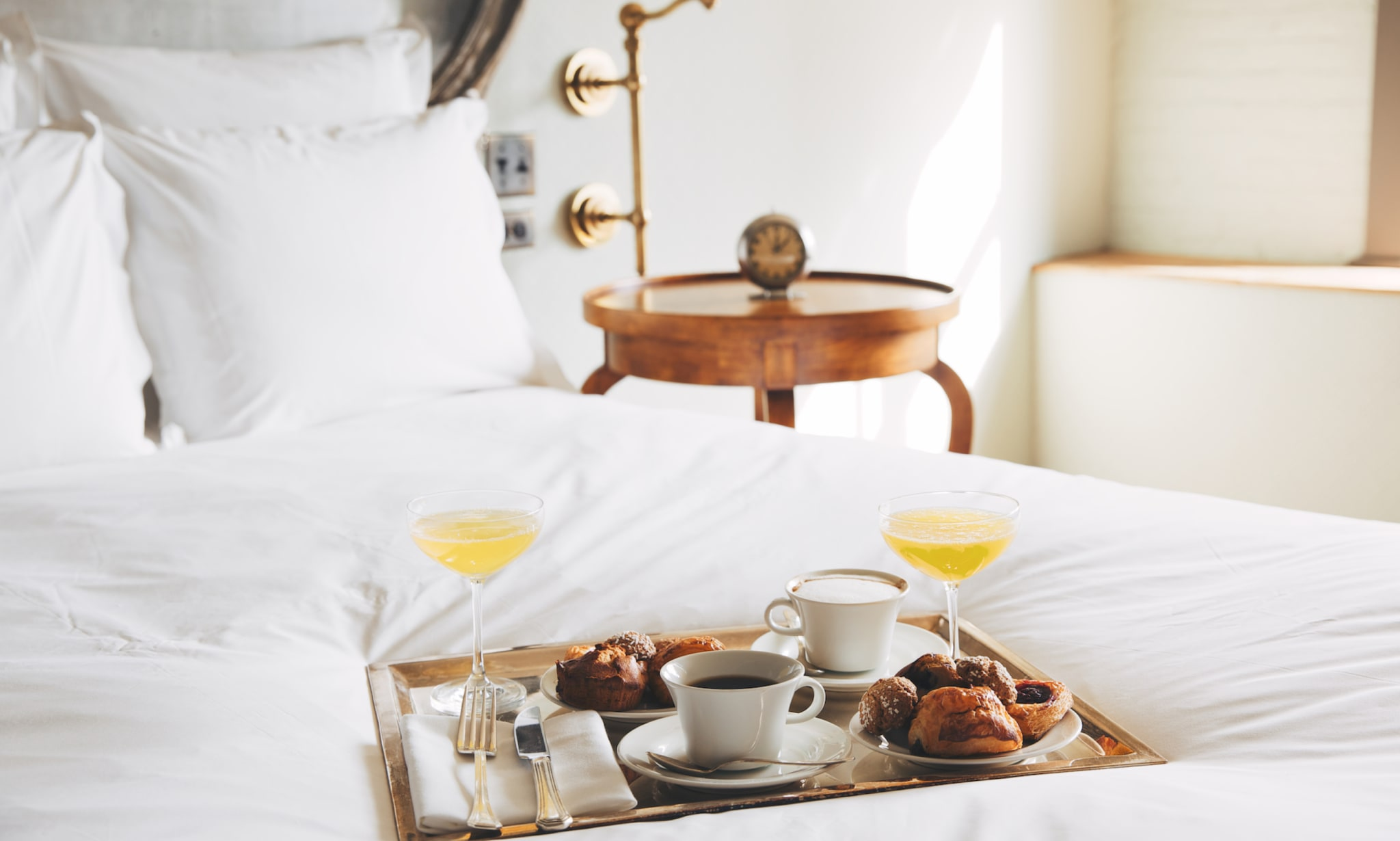 Breakfast room service on a tray on a bed.