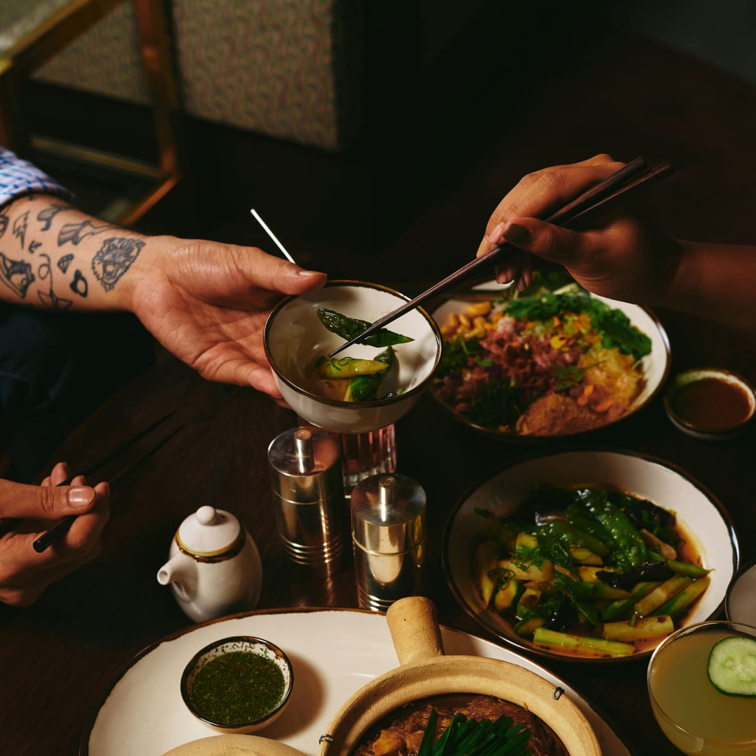 Two people share Asian food.