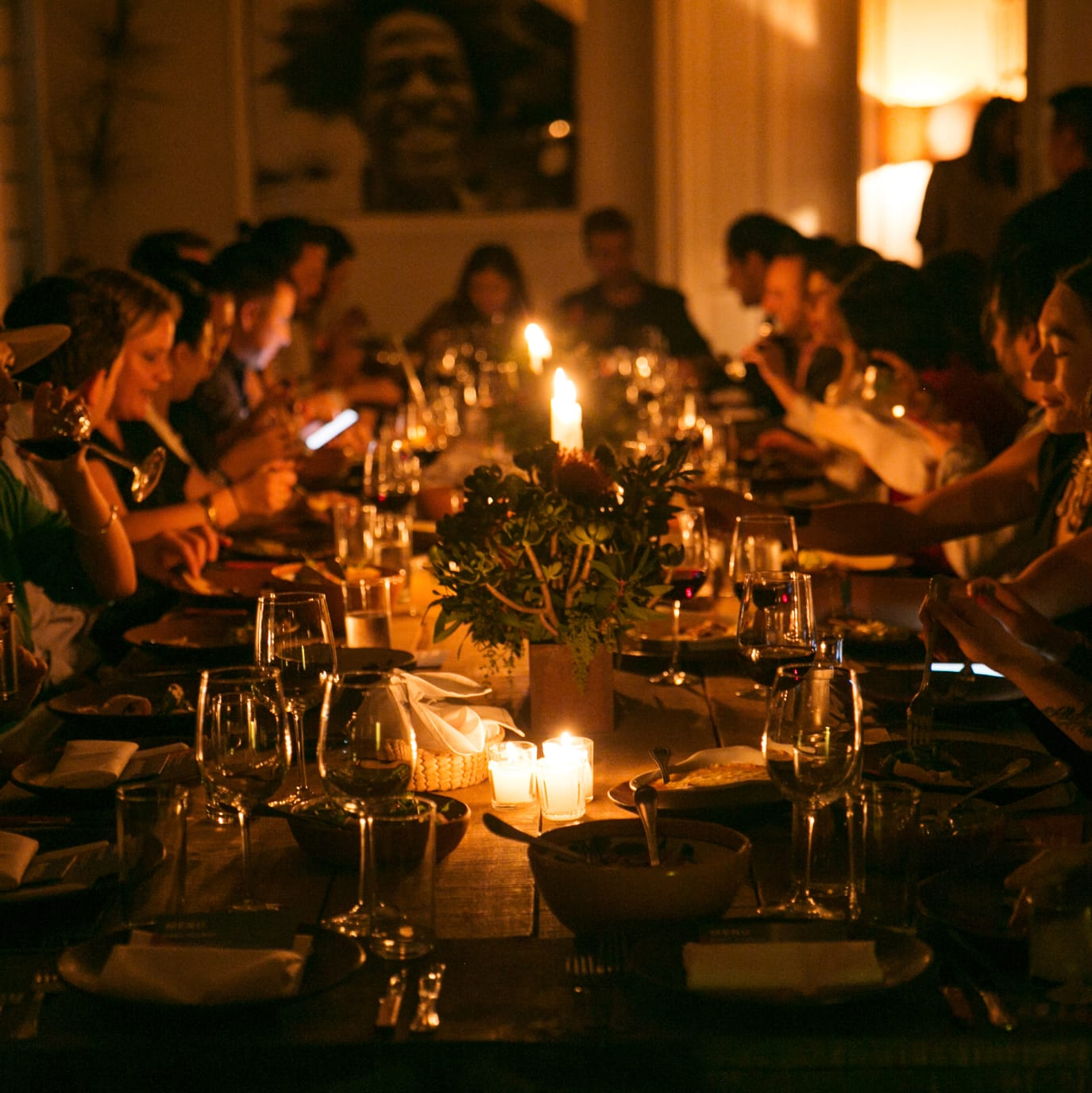 A large group of people eating dinner and chatting around a candle lit table.