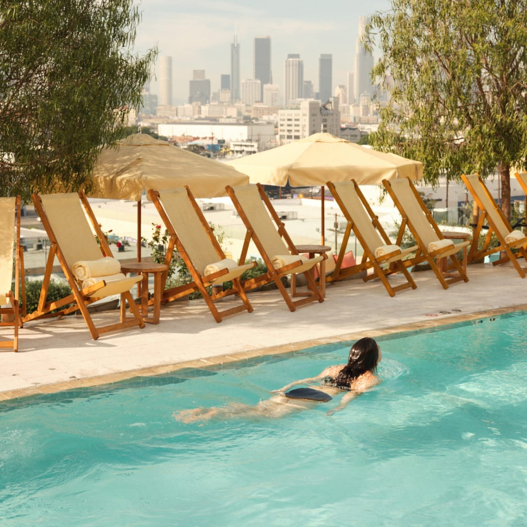 A woman swimming in a rooftop pool with a city in the background.