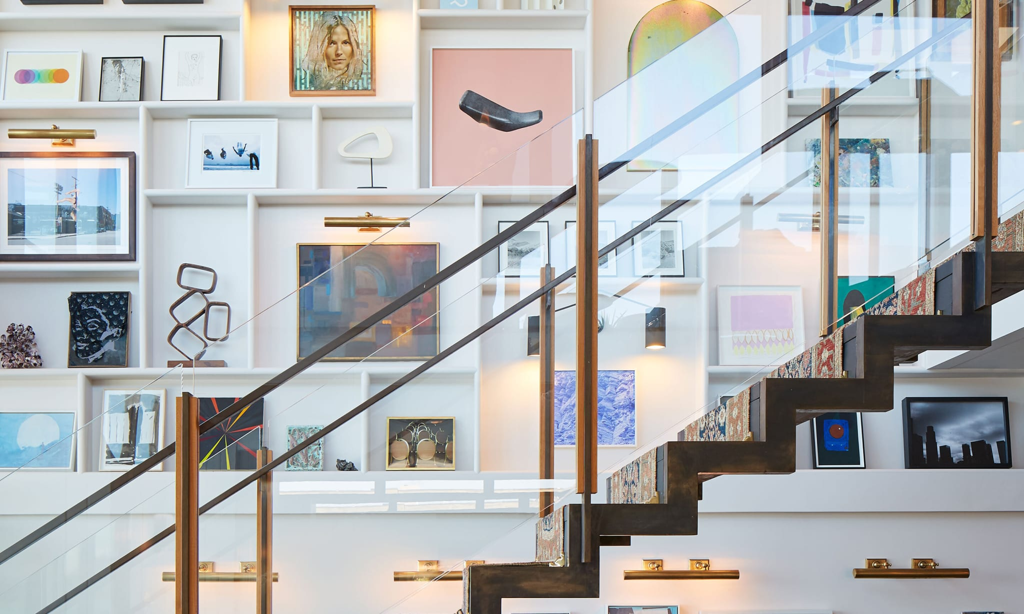 wall of framed art by staircase