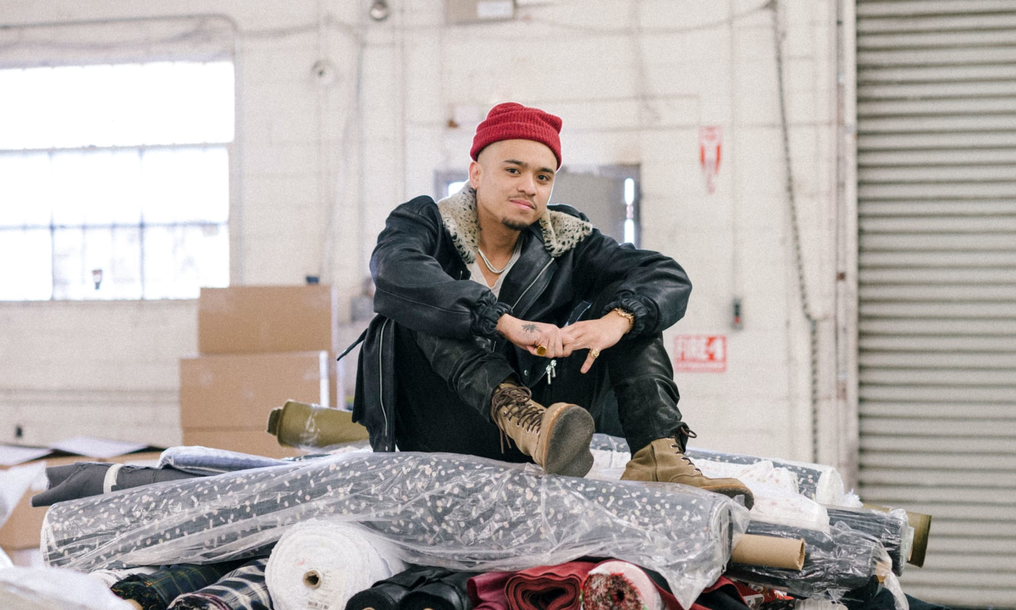 A man in a red beanie hat sitting on rolls of fabric.