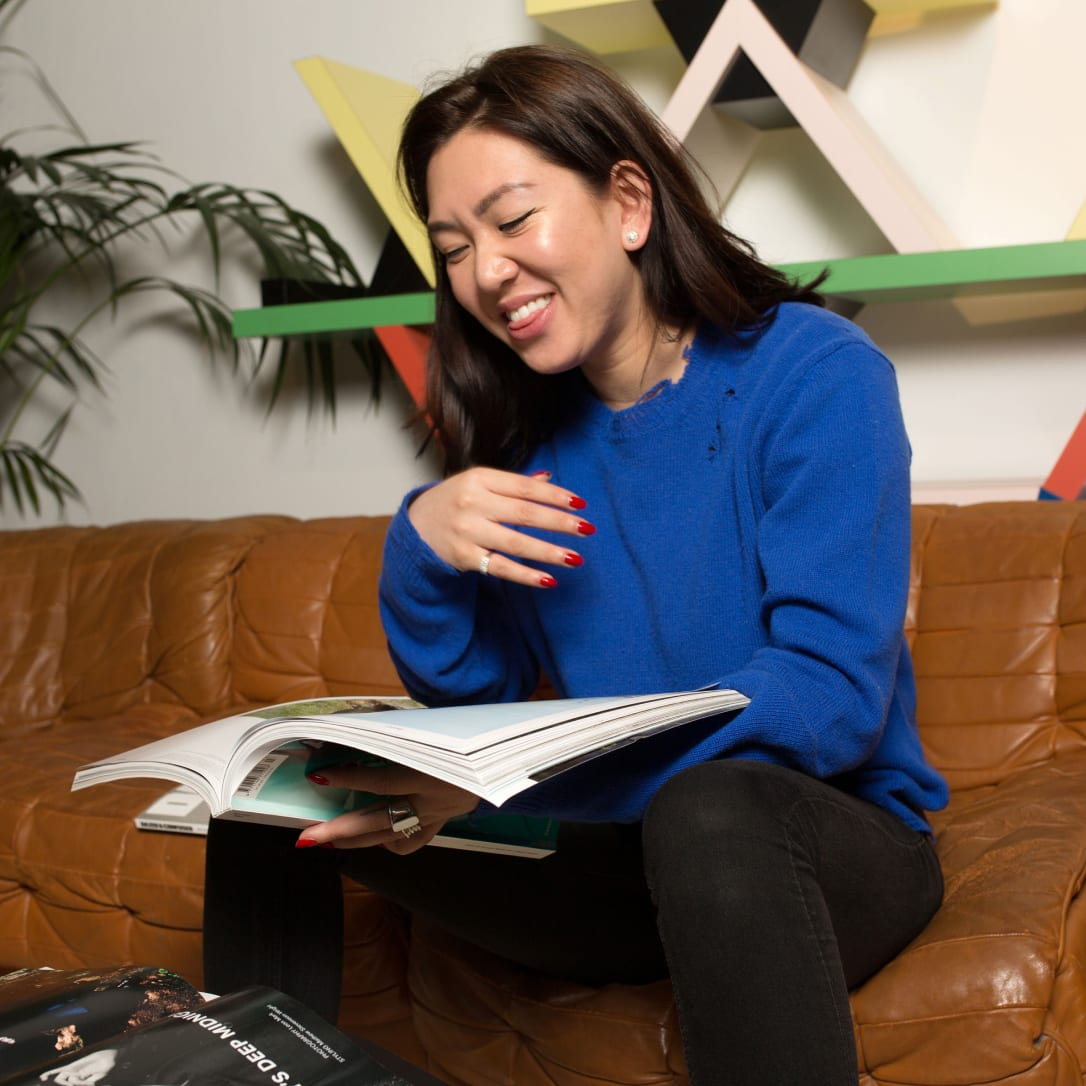 A woman laughs while flicking through a magazine on a sofa.