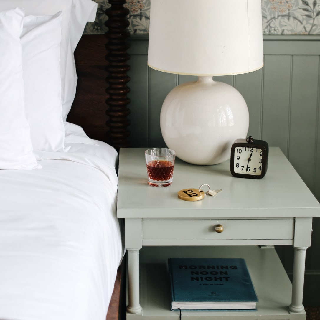 The corner of a bed and side table with a cocktail and room key on it.