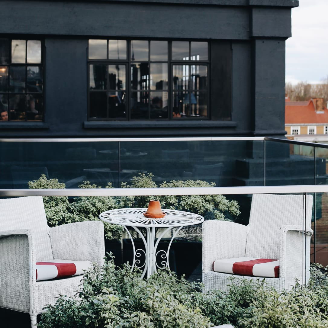 A outdoor terrace with seating and table and plants overlooking a black building.