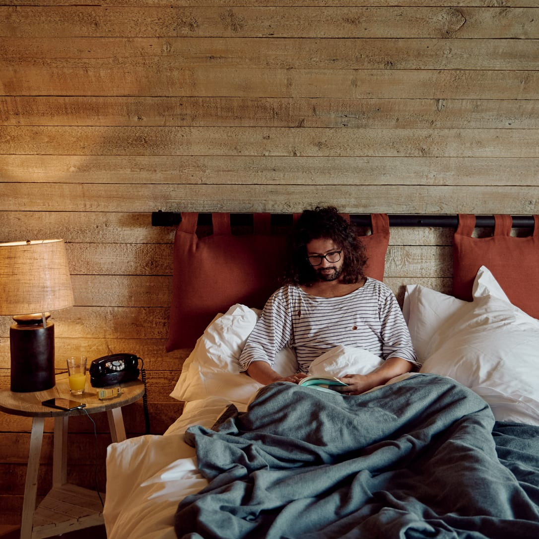A man reading a book in bed in a wooden bedroom.
