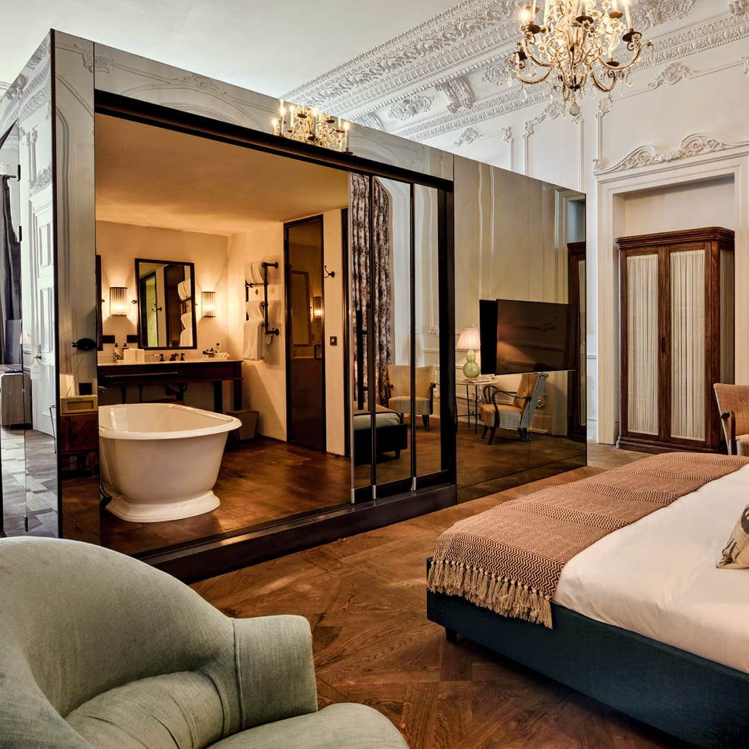 A large, high-ceilinged, ornate bedroom with a large mirrored box containing a bathroom within it.