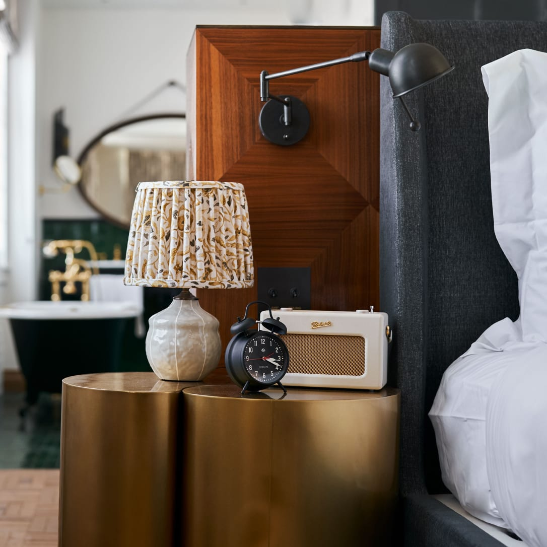 A bedside table with a bathroom in the background.