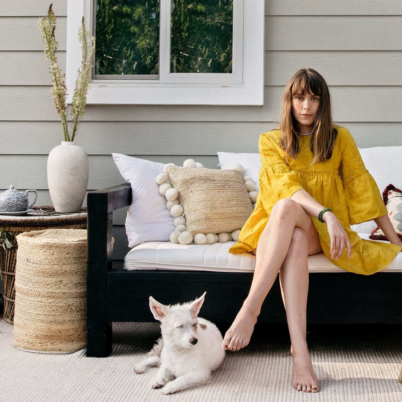 woman in yellow dress sat on outdoor sofa with dog at her feet