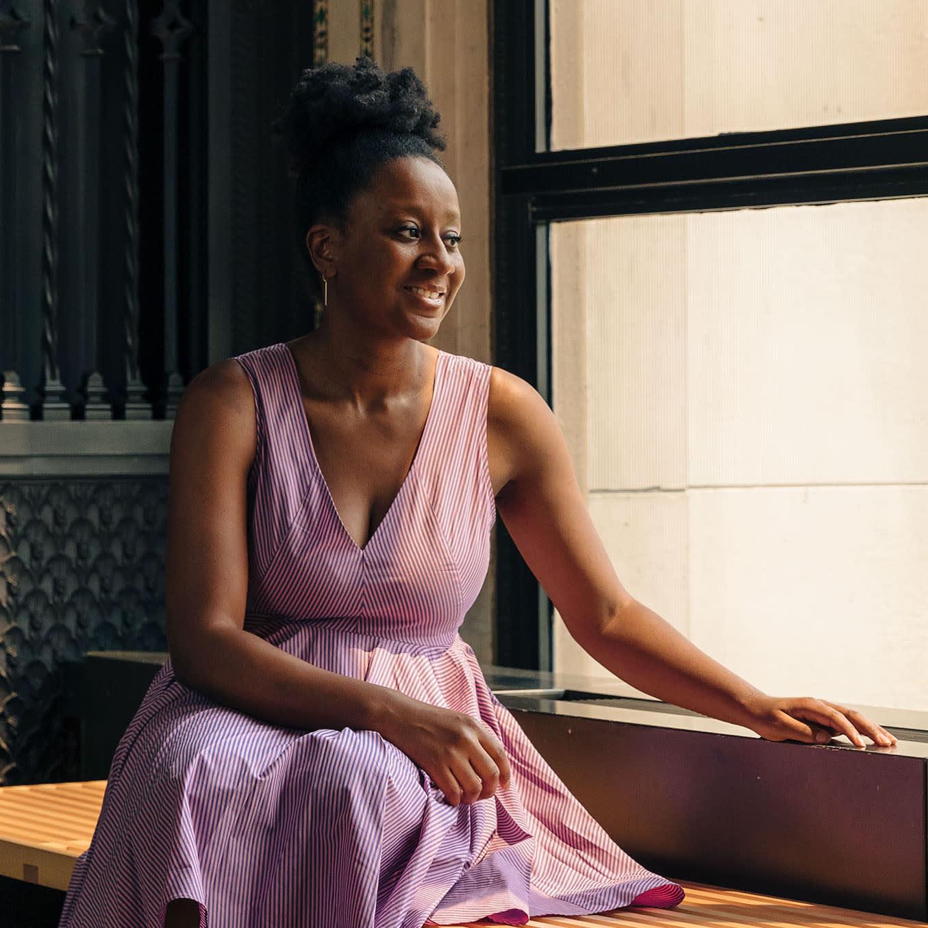 woman in purple dress sitting by window