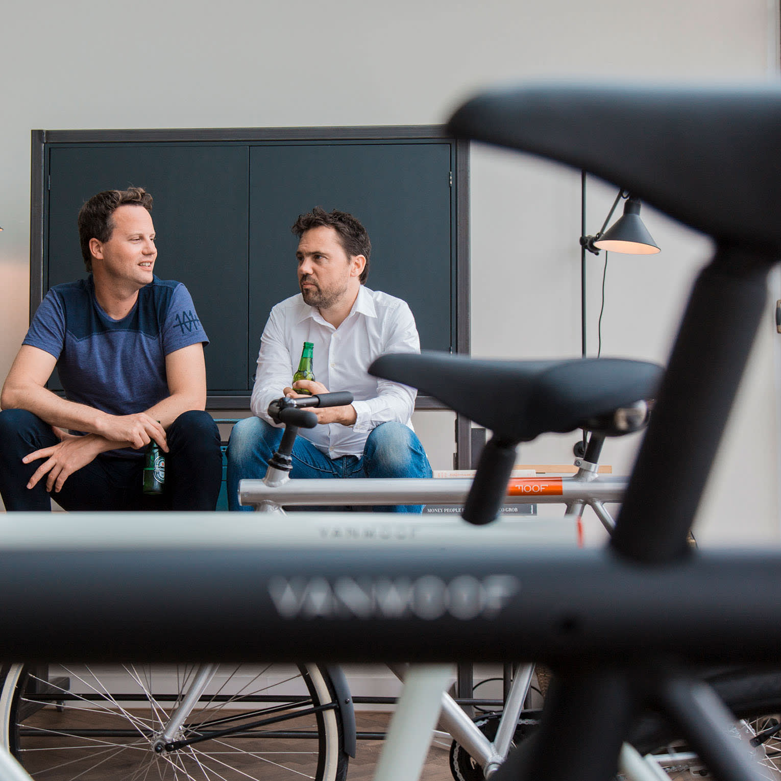 two men sitting in office behind a bike
