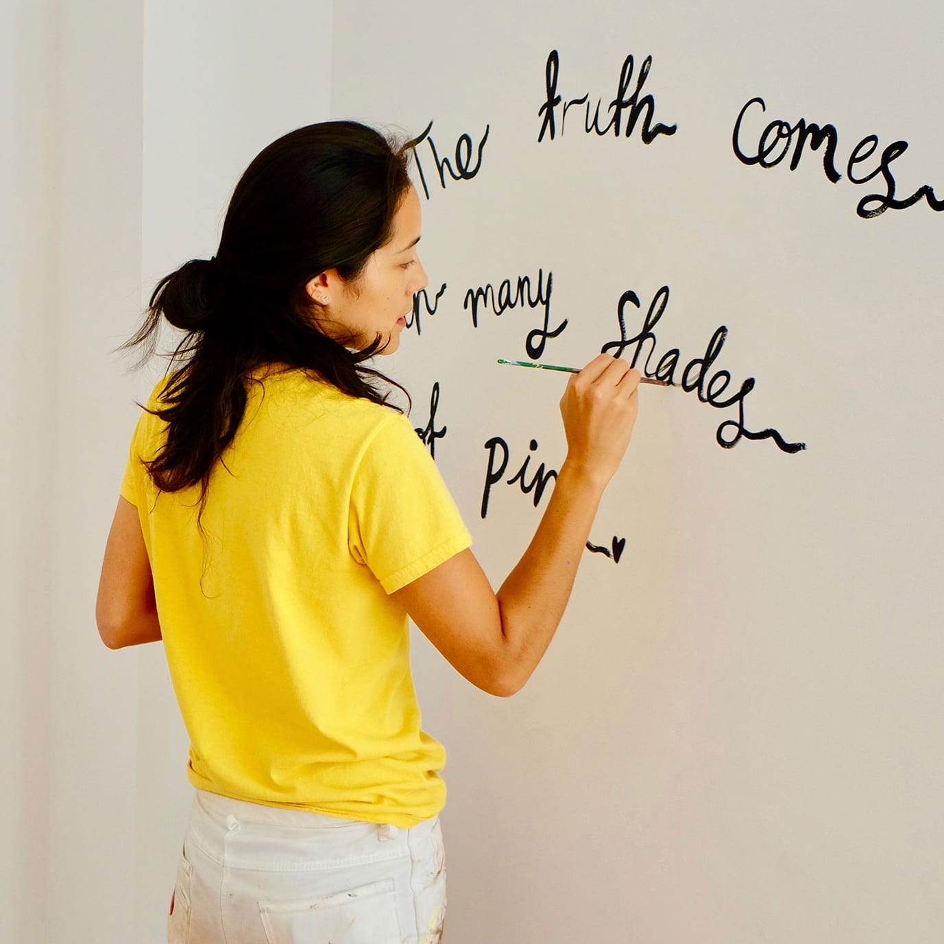 woman painting words on a wall