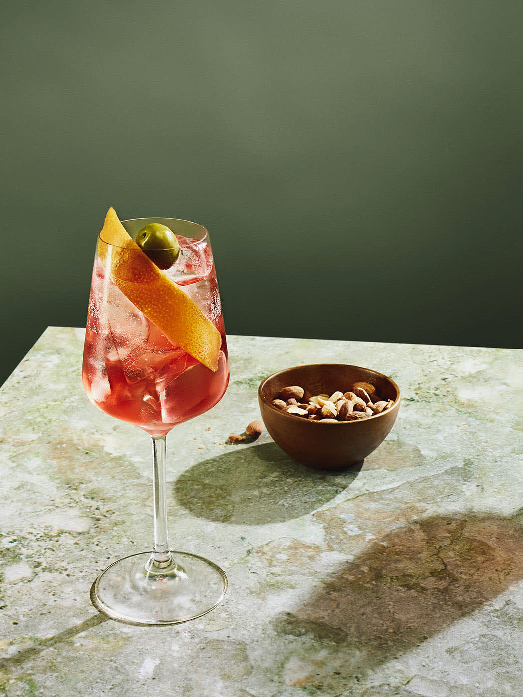 A colourful cocktail on table with olives