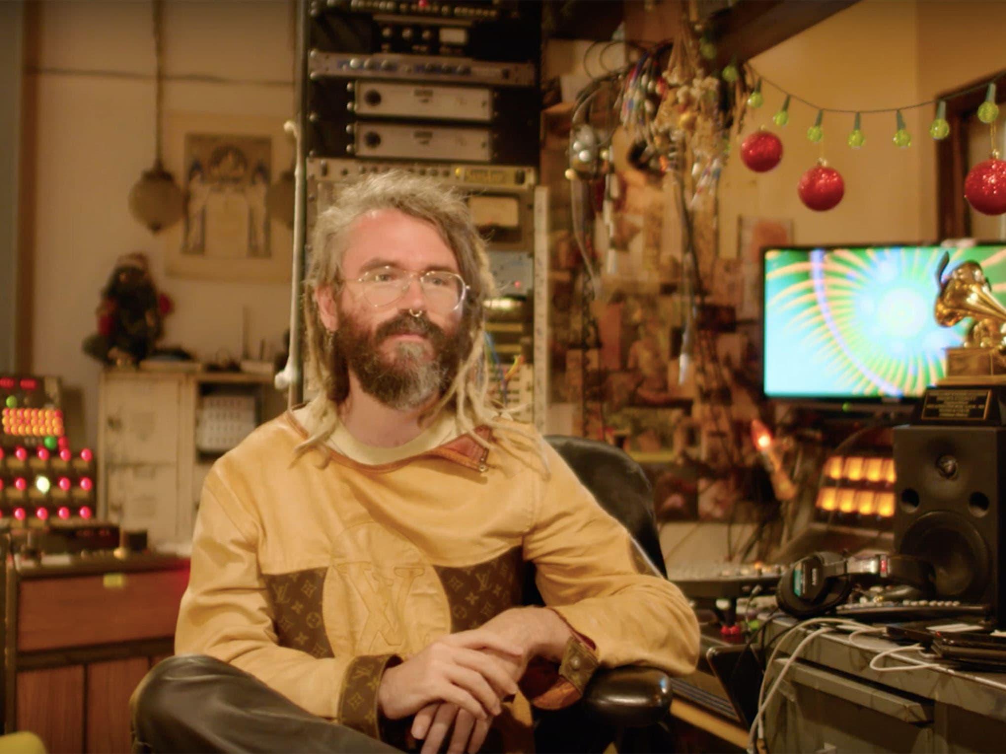 Bearded man in sweatshirt sitting in studio with Grammy award next to him