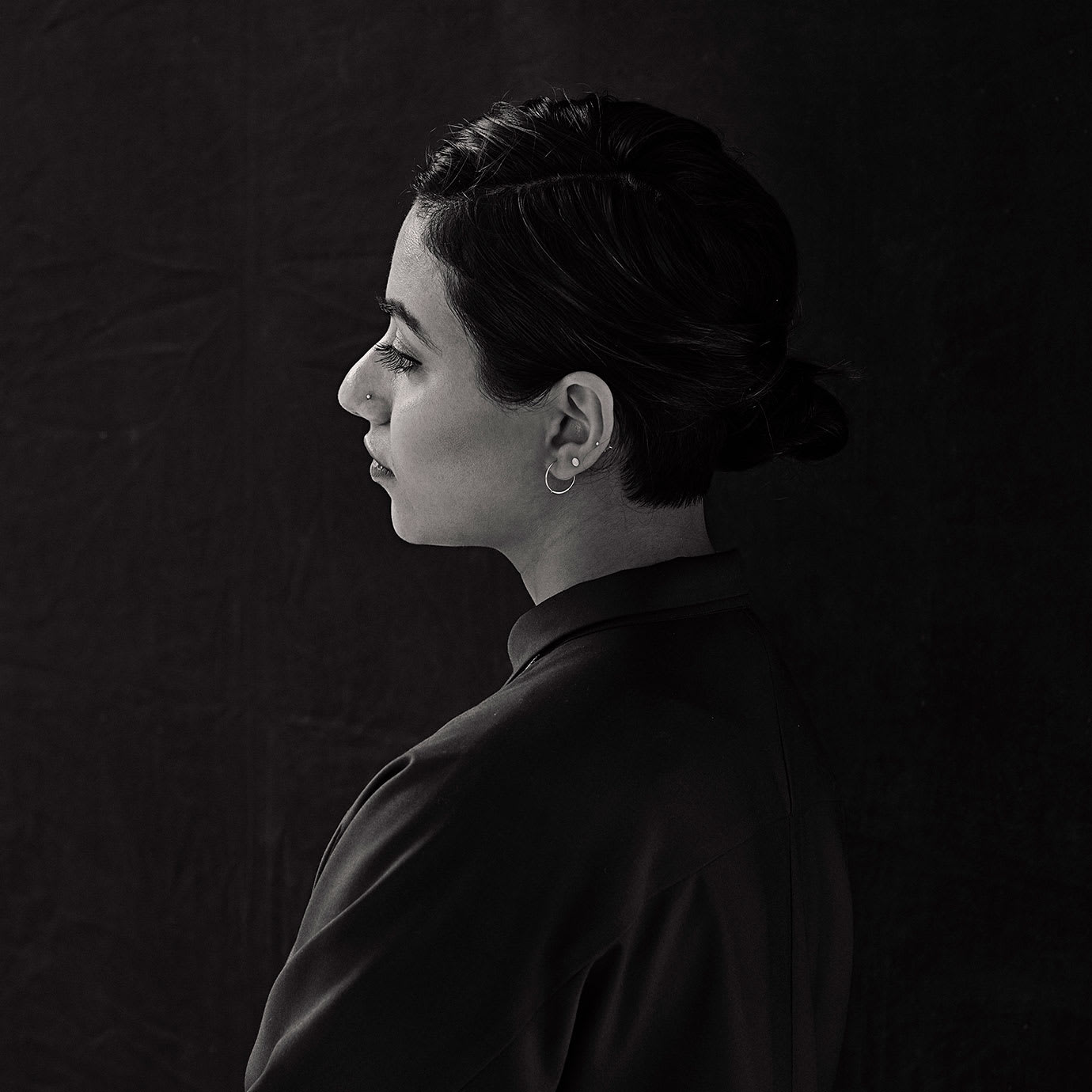 The back of a woman with the side of her head showing in profile.