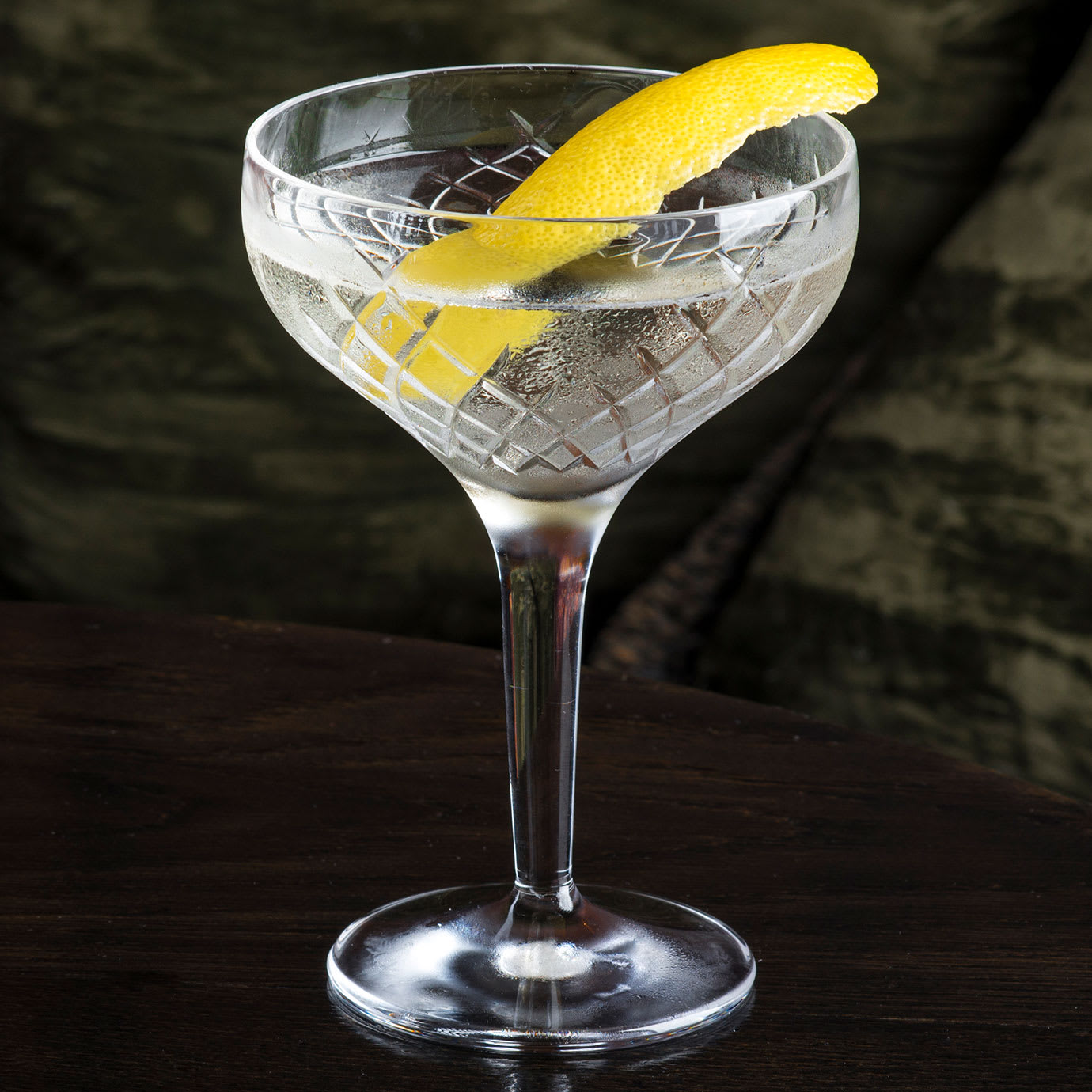A cocktail with a slice of lemon peel in it.