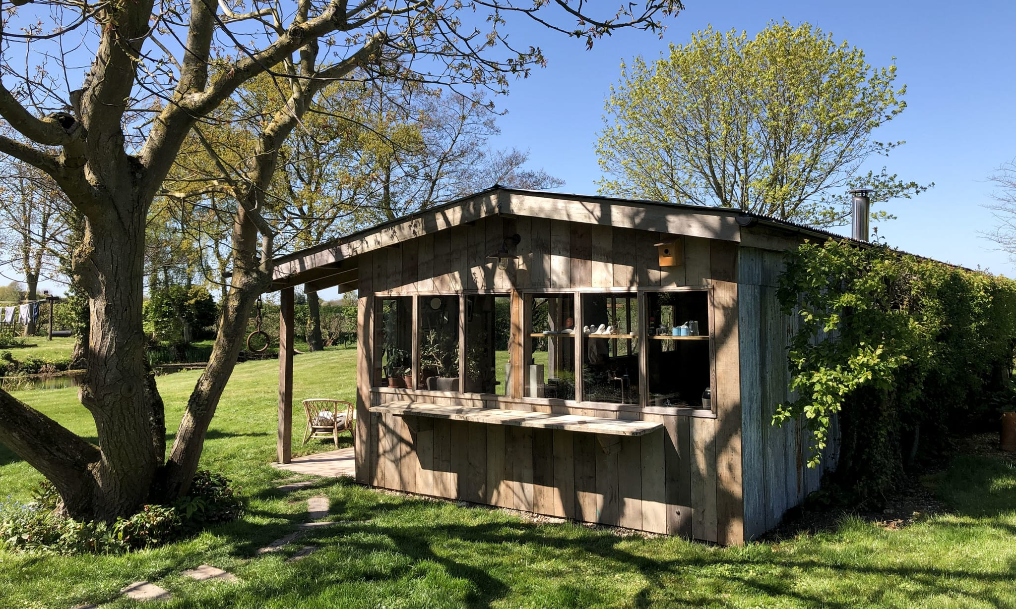 The exterior of a wooden shed-like building in a garden with trees.