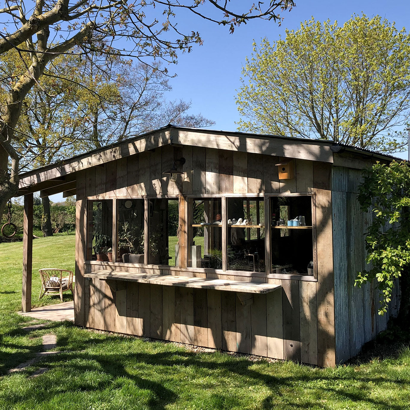 A large wooden studio in a large sunny garden.