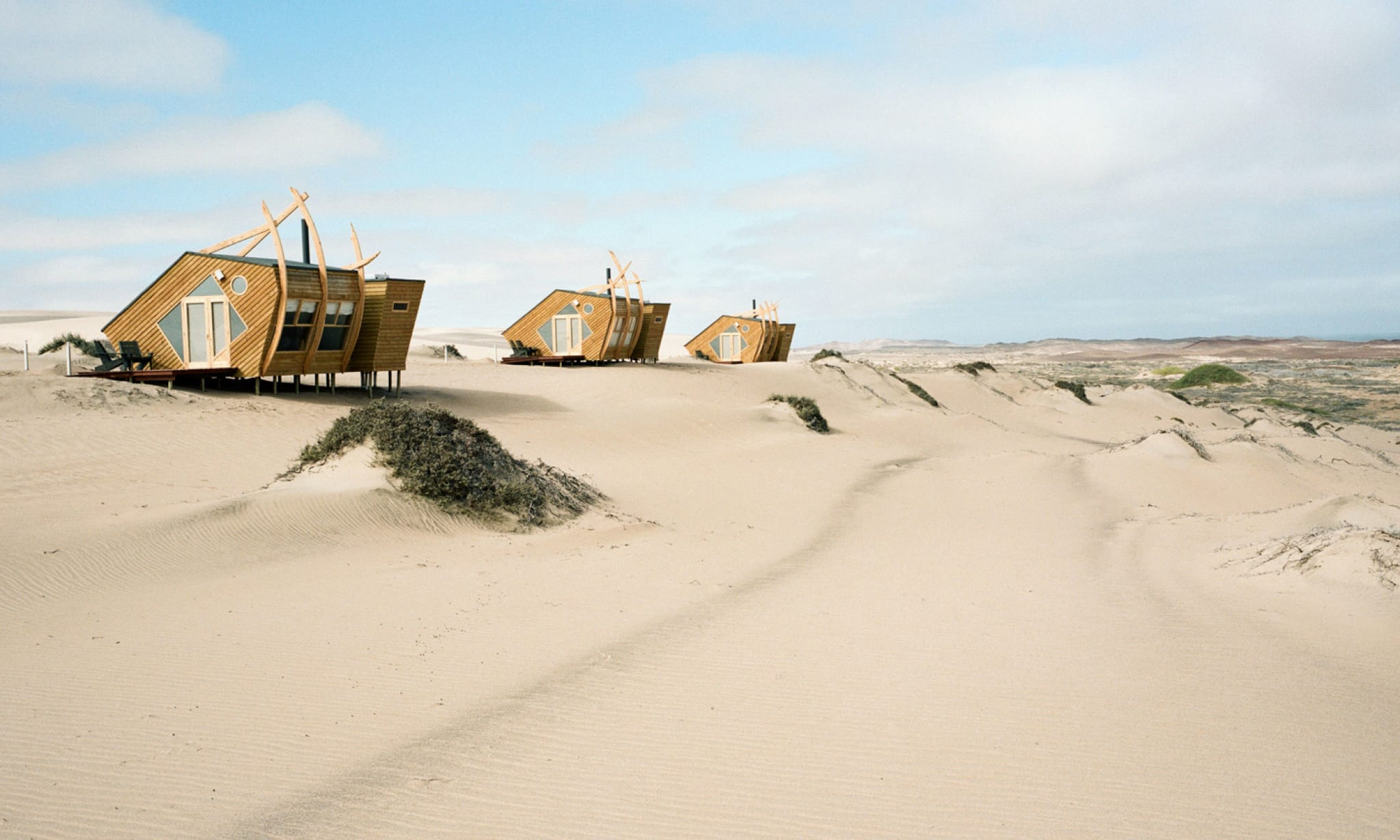 Three wooden buildings perched on a dune in the desert.