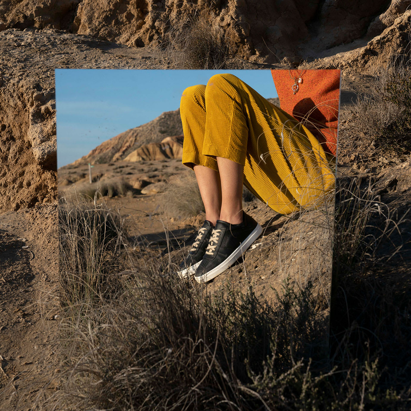 A man and shoes reflected in a mirror in the desert.