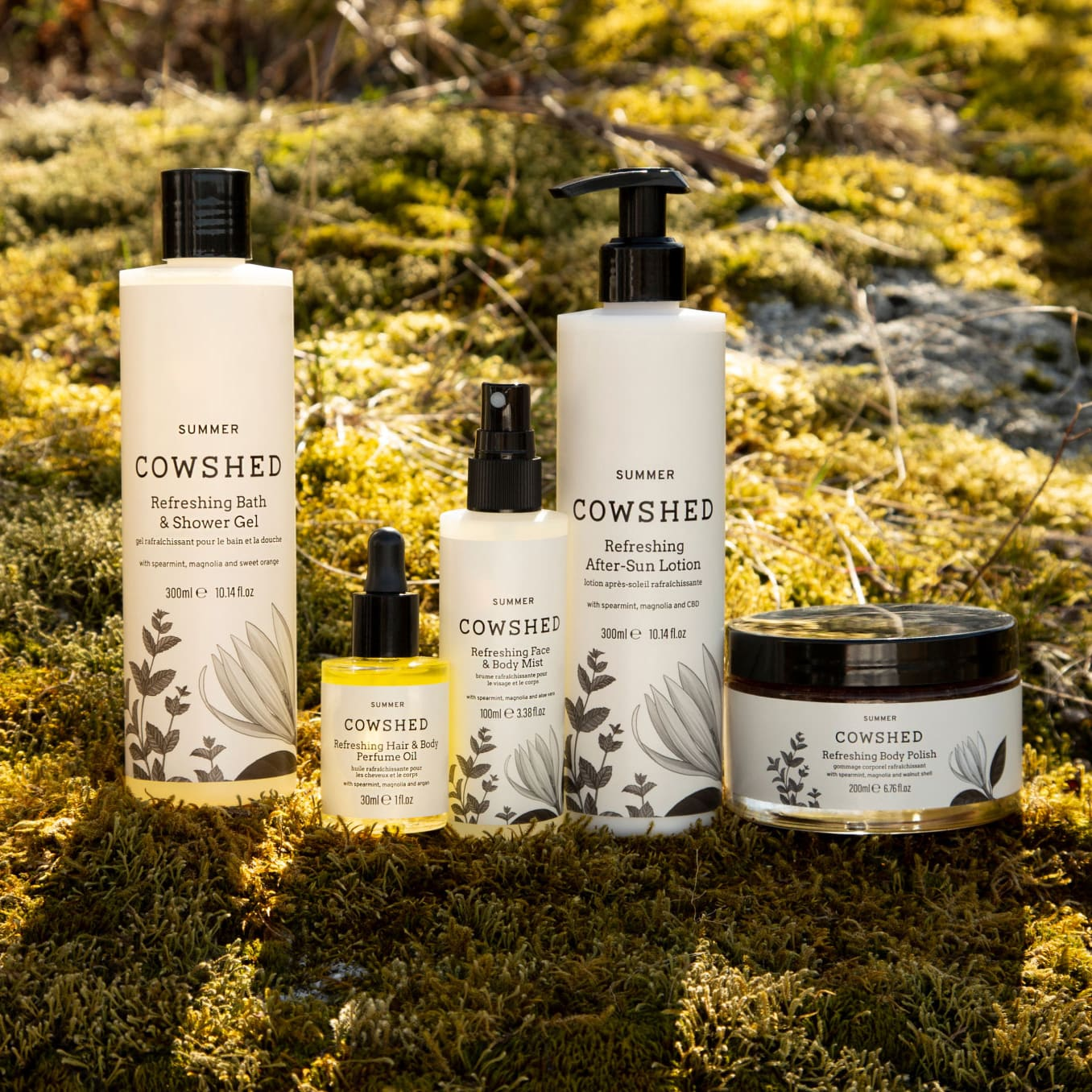 five cowshed beauty products on a mossy rock