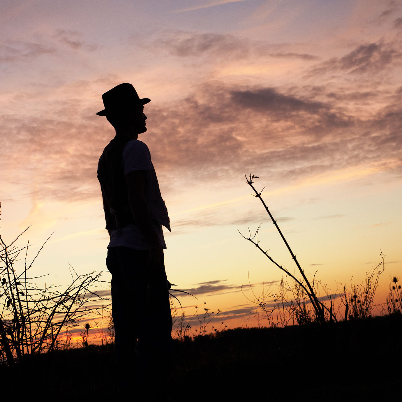 The silhouette of a man standing in a field at sunset.