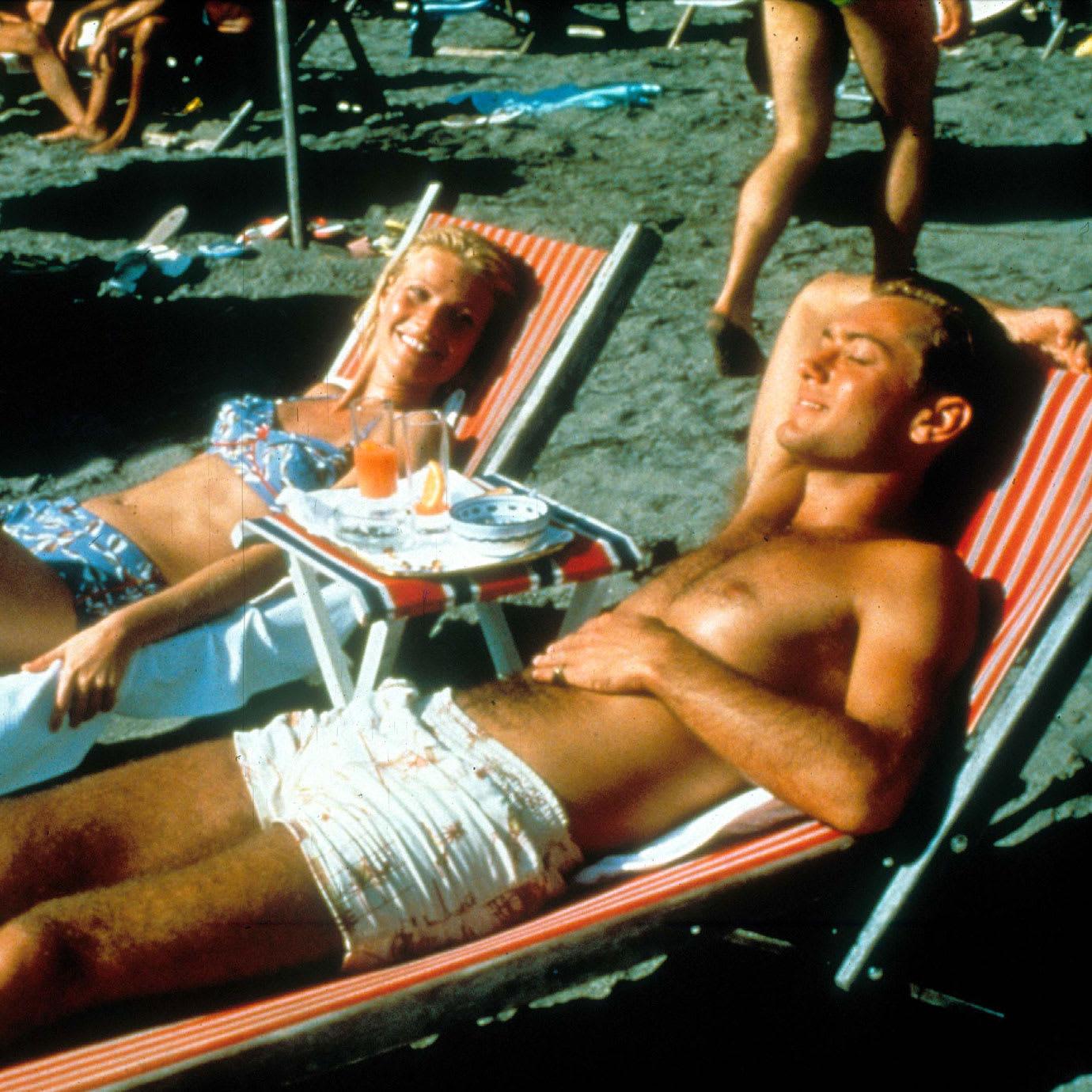 A man and a woman sunbathing on a beach.