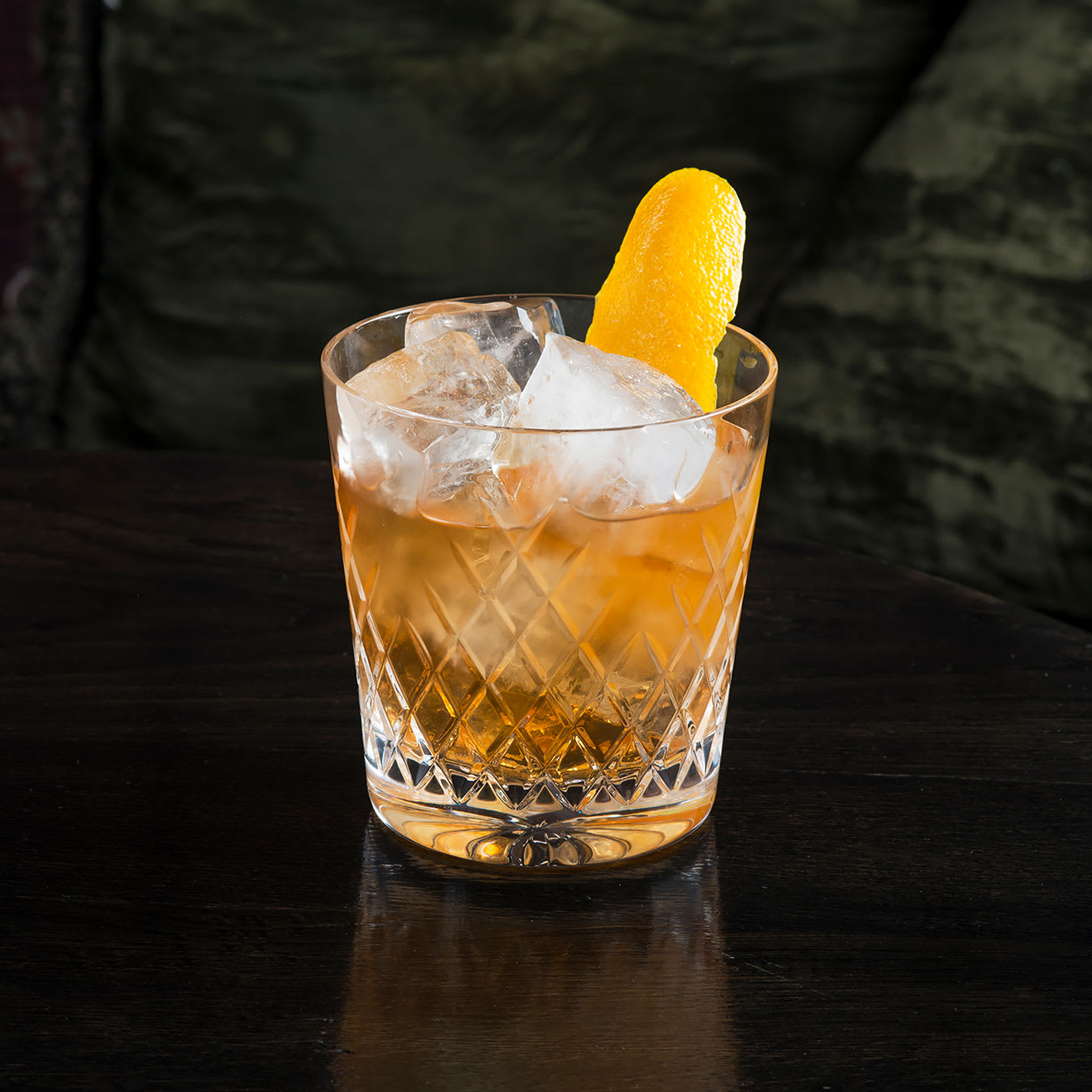 A cocktail with a slice of orange peel in it.