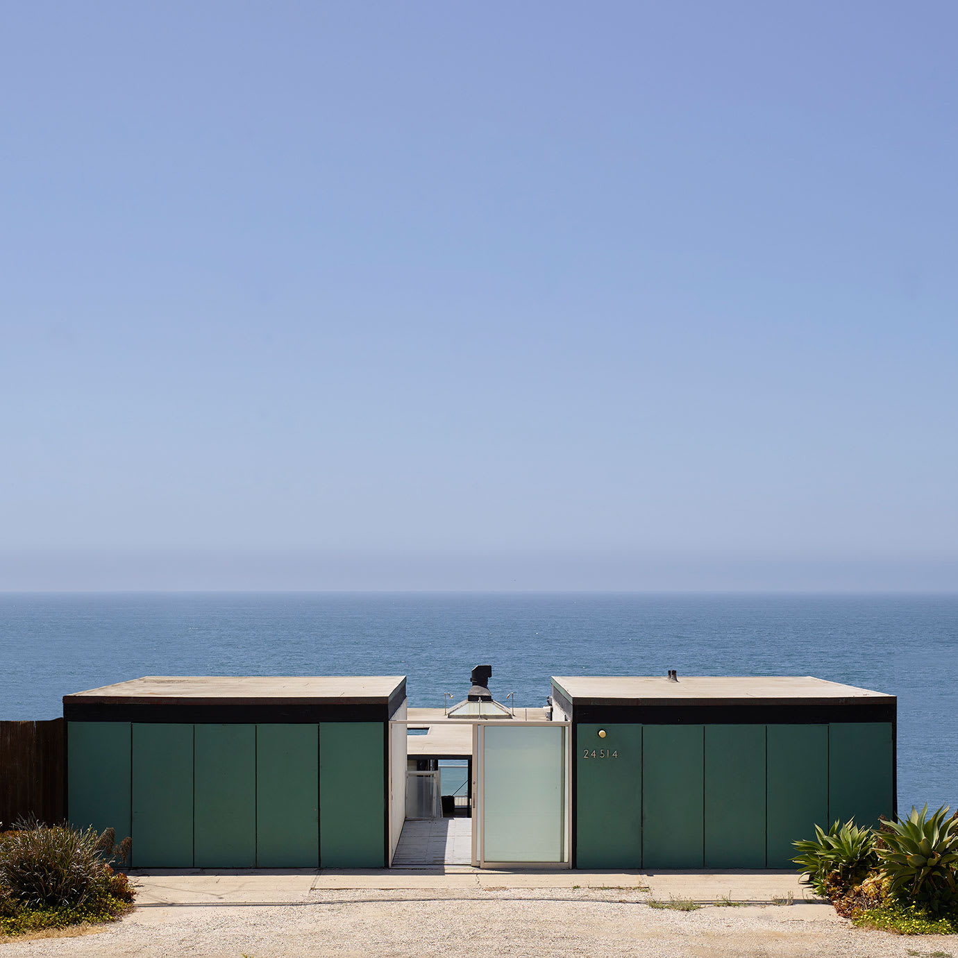 The exterior of a modernist house overlooking the sea.