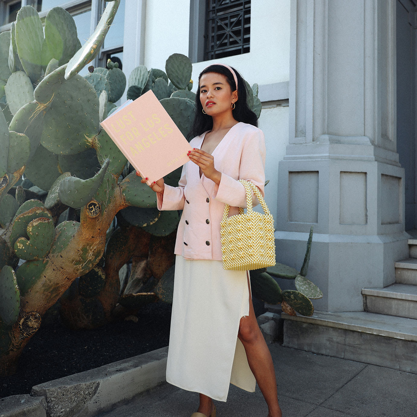 A woman holding a book in front of a white building.