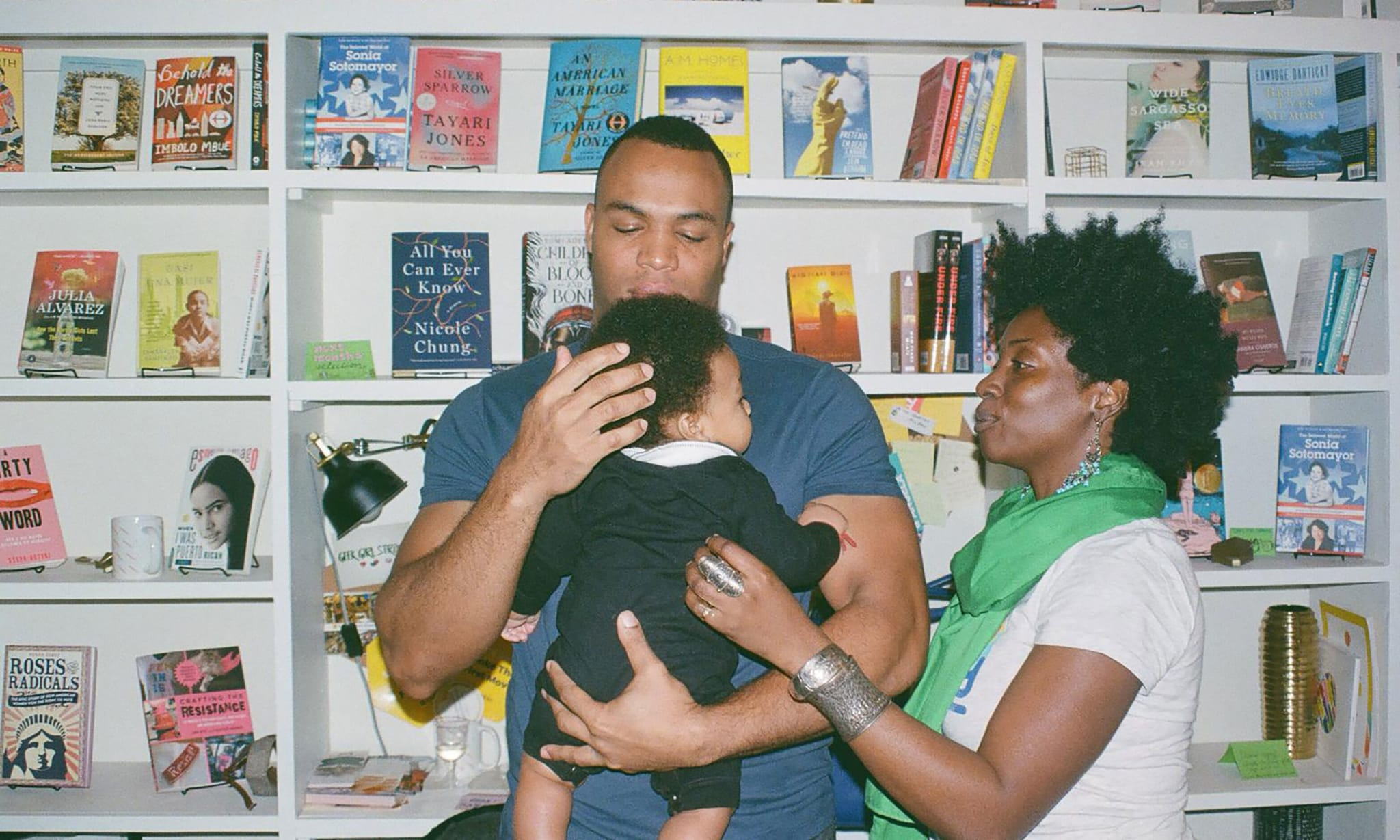 Parents and their child standing in front of a book shelf.