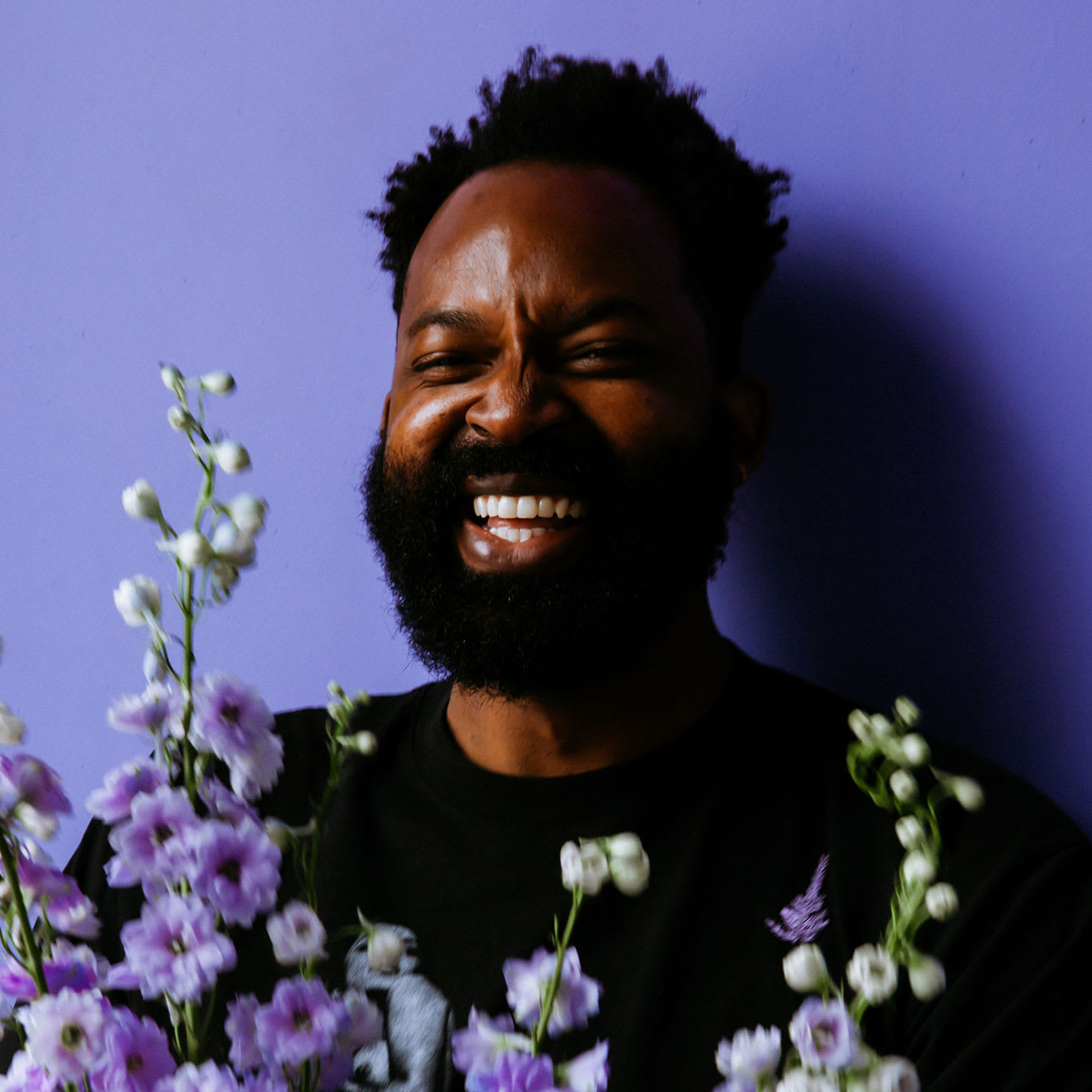 A man smiling in front of a purple background while holding flowers.
