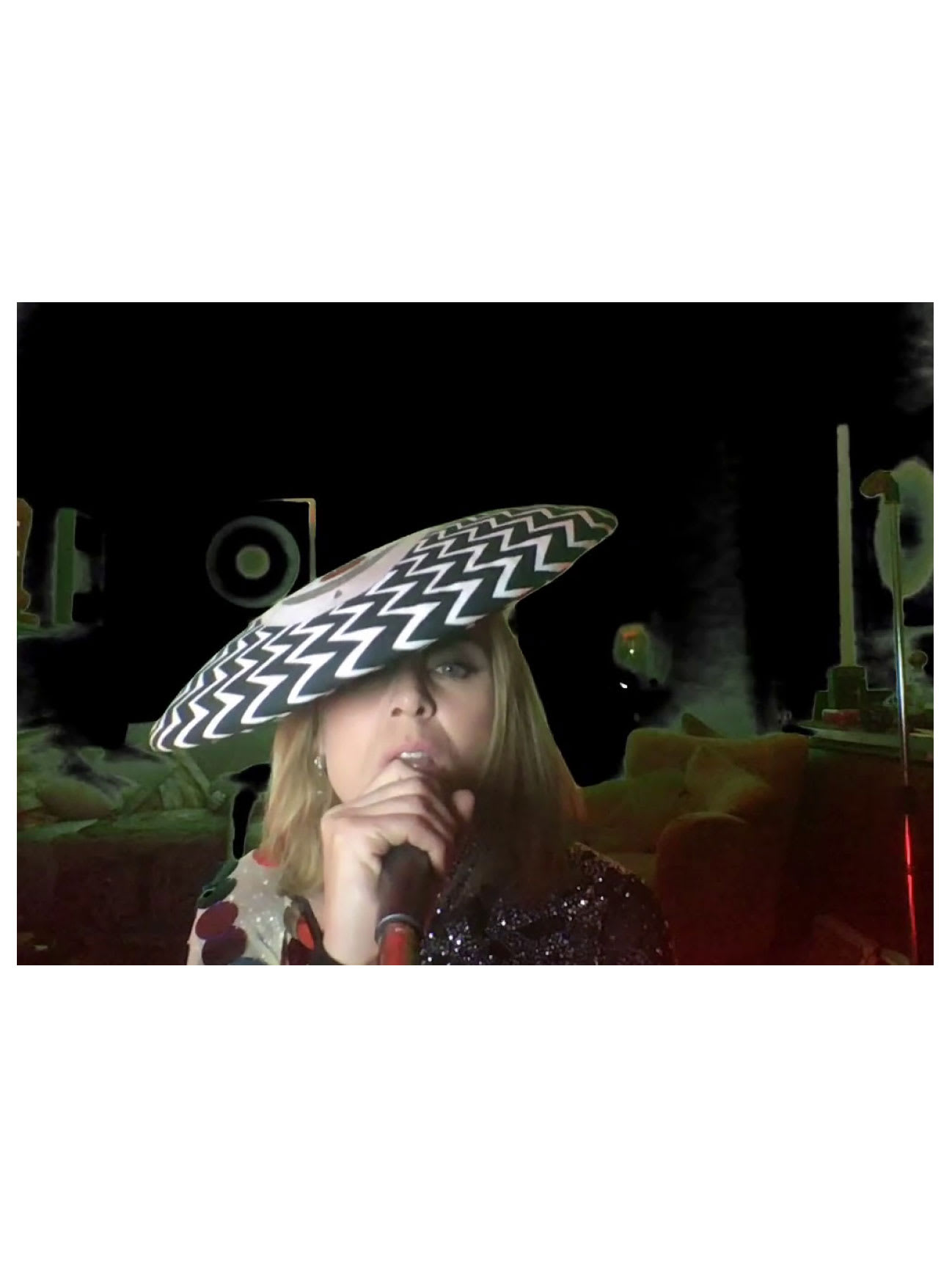 A woman singing in a dark room holding a microphone and wearing a zigzag patterned hat.