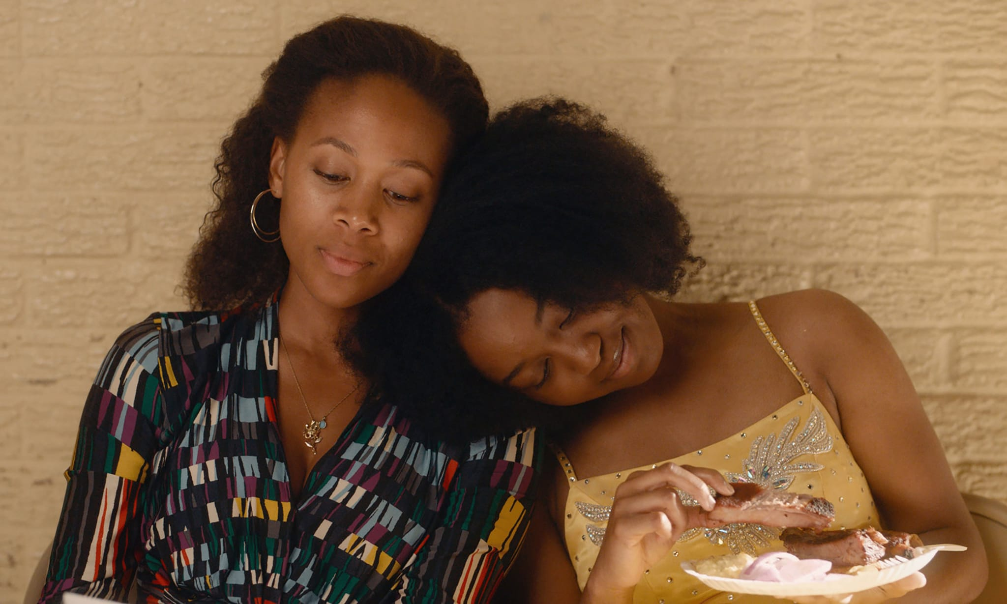 A woman resting her head on another woman's shoulder.