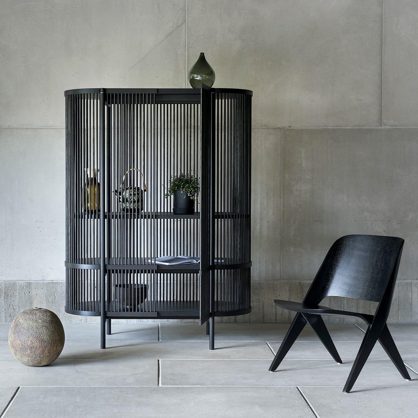A black cabinet and a chair in a stone room.