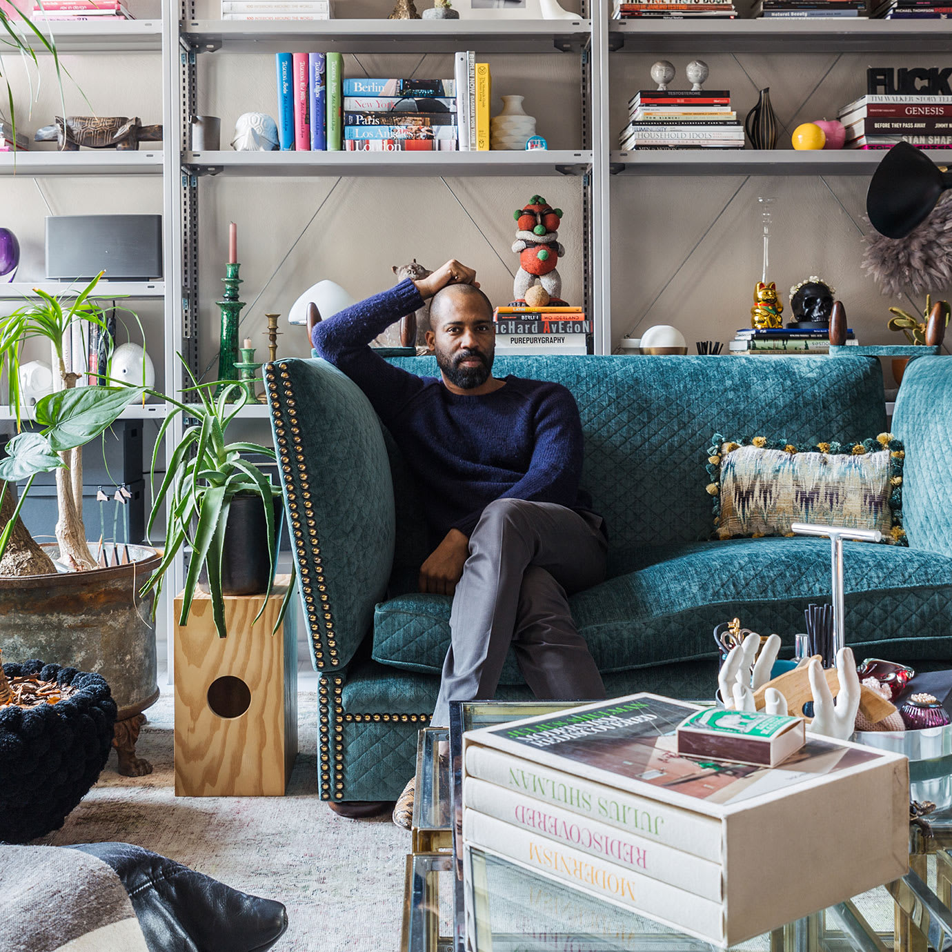 A man sitting on a blue sofa in an apartment full of decorative items.