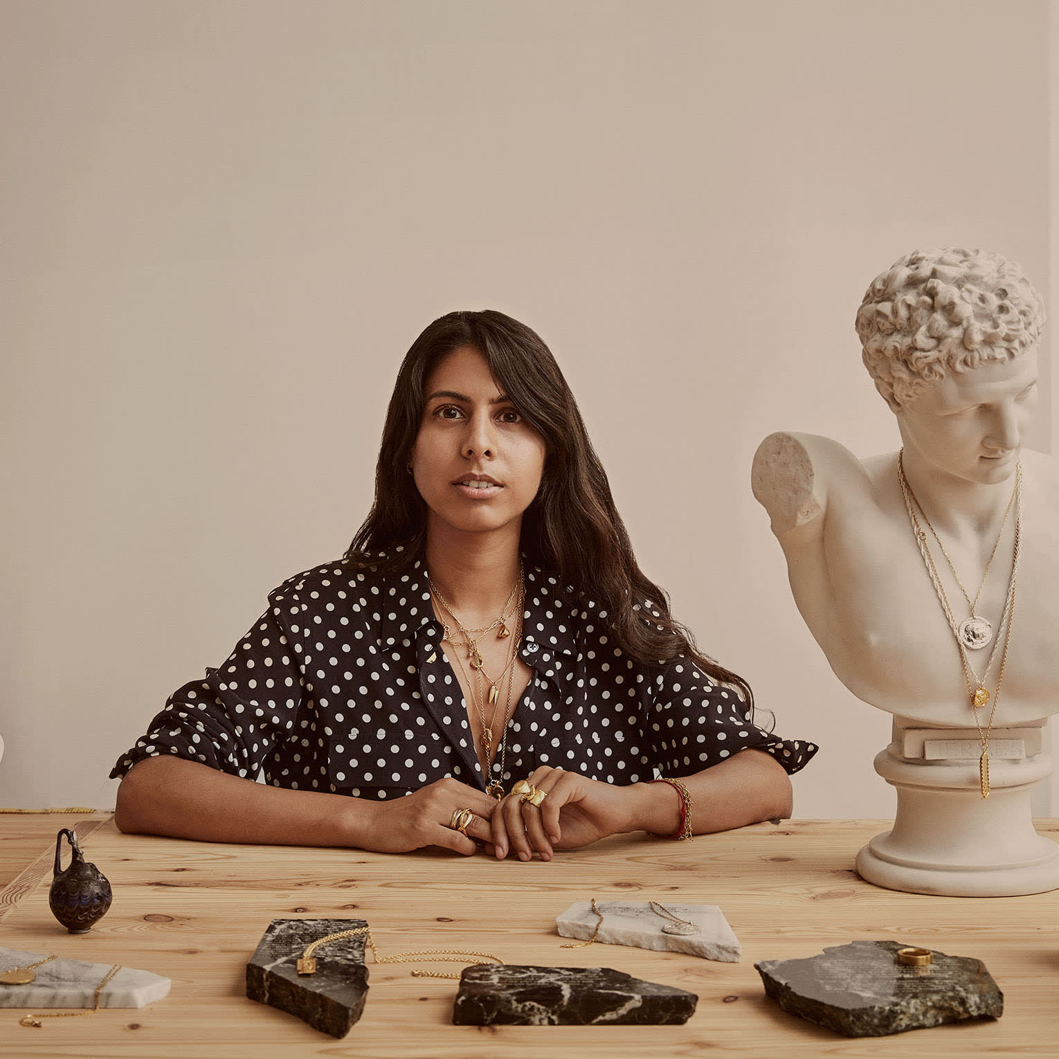 woman with jewellery in front of her and bust statue next to her