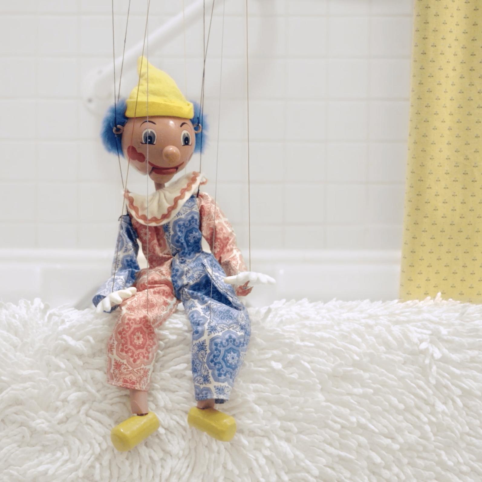a puppet on edge of bathtub.