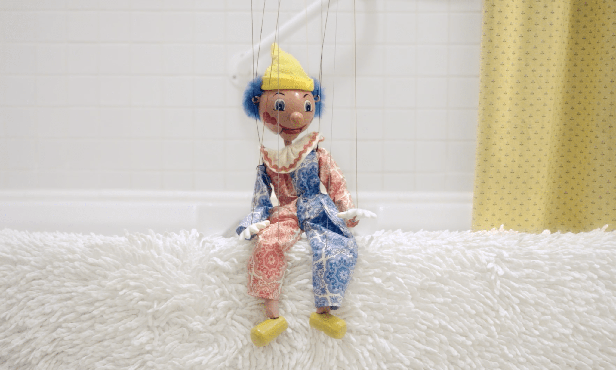 a puppet on edge of bathtub.