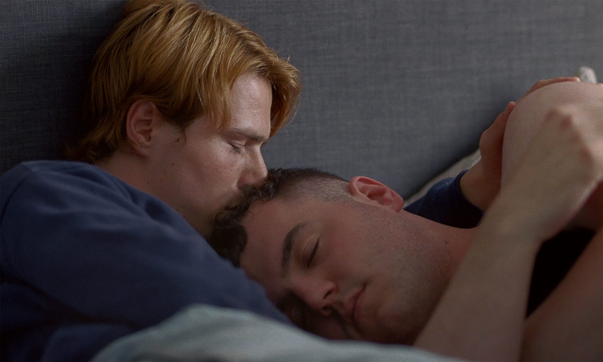 One man comforting another man in bed.