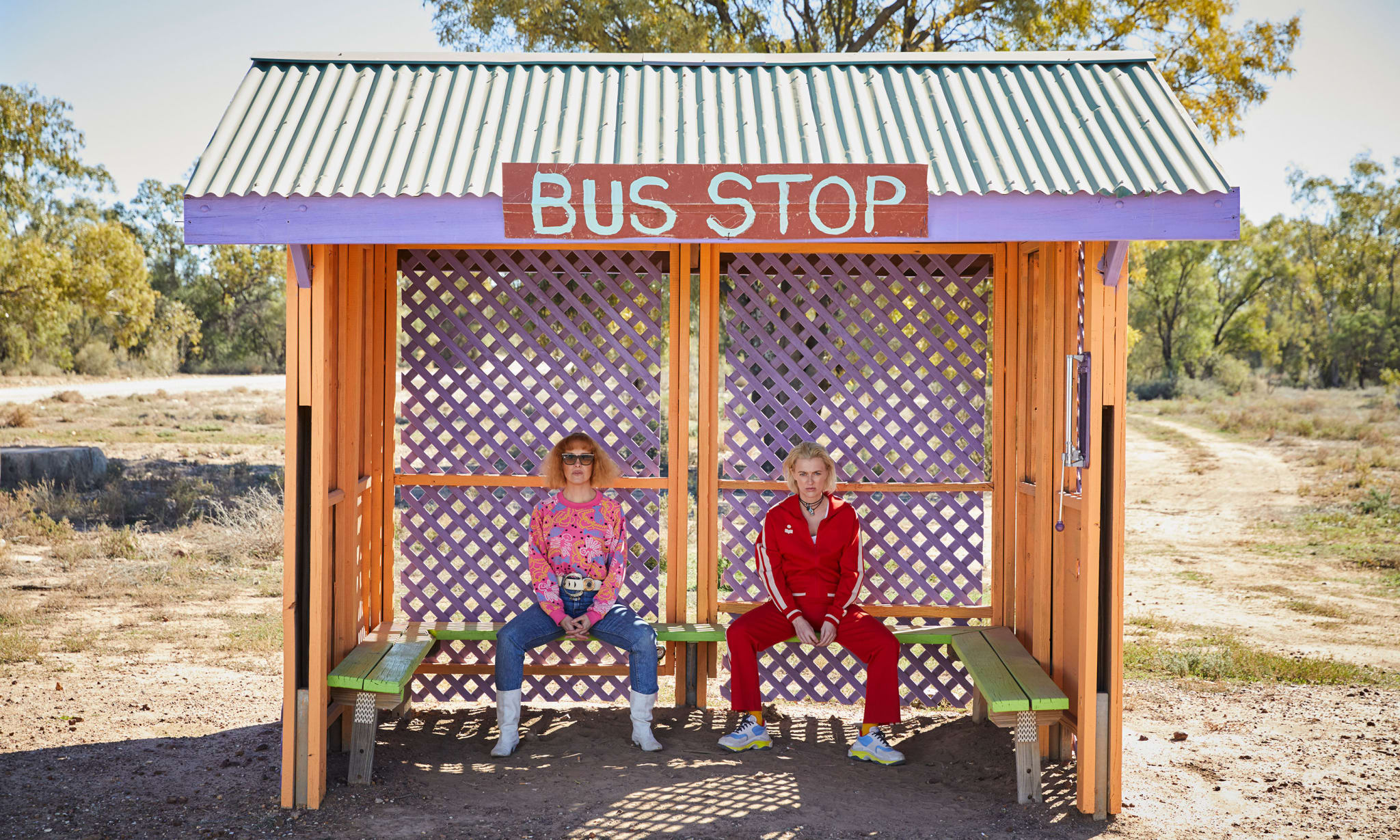 Two women sat in a colourful bus stop in the desert.