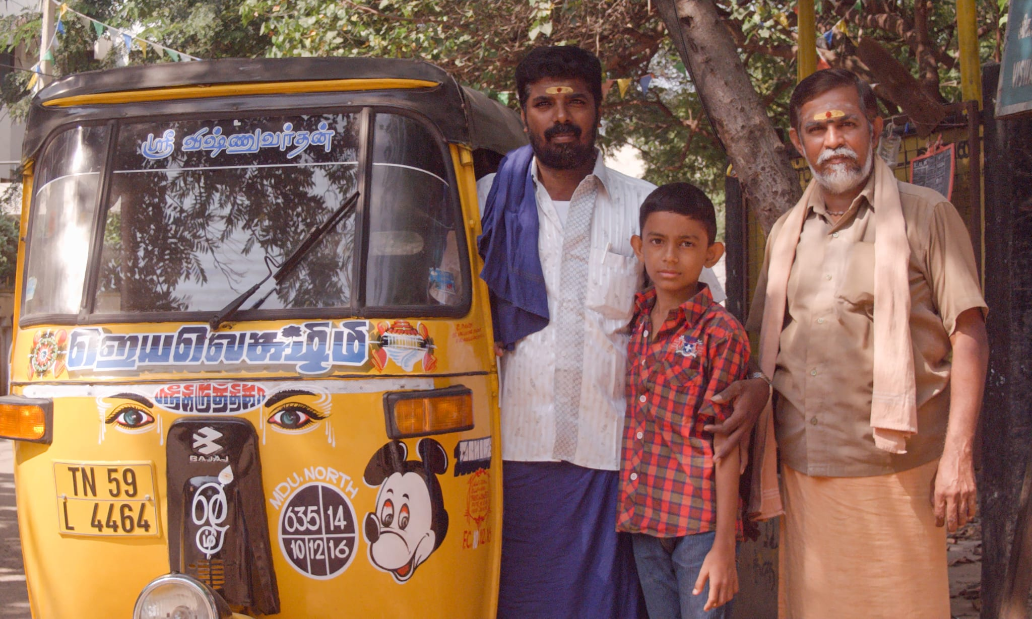 Two men and a boy standing next to a yellow tut-tut with a sticker of Mickey Mouse on it.