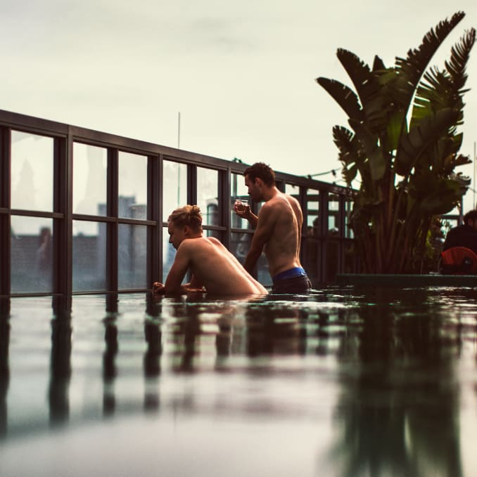 A rooftop swimming pool with two people talking in it.