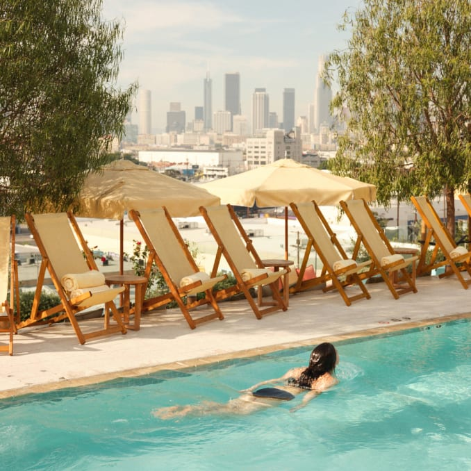 A woman swimming in a rooftop pool overlooking Downtown Los Angeles.