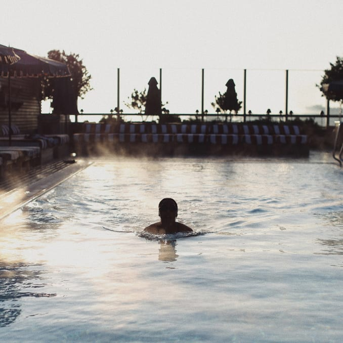 A person swimming in a steaming rooftop pool.