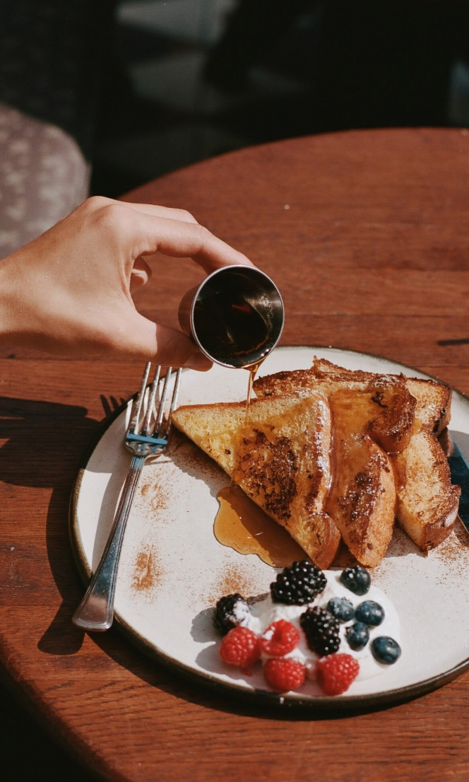 A person pours syrup onto french toast.