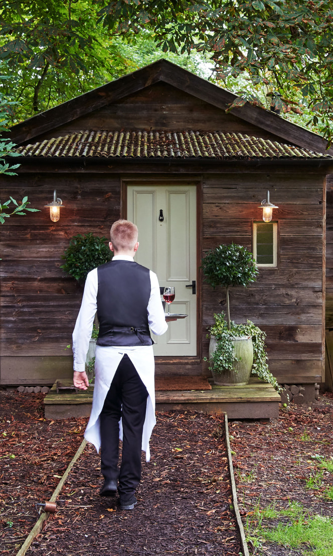 A waiter delivers room service to a wooden cabin.